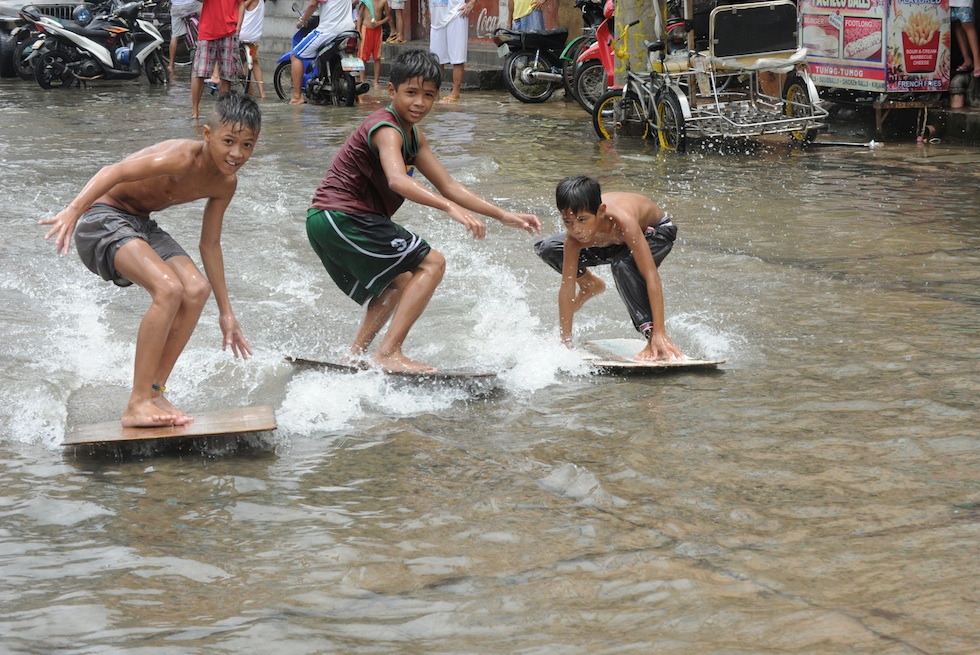 Children use plywood to surf in a floode